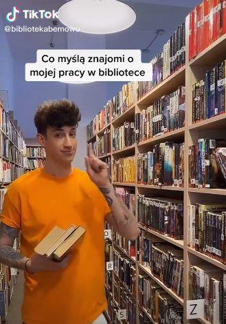 Na zdjęciu widoczny mężczyzna w pomarańczowej koszulce trzyma trzy książki w tle widoczne regały biblioteczne z książkiami