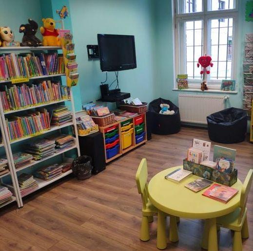 Na zdjęciu widoczne pomieszczenie o nazwie Kosmiczna sala w oddziale dla dzieci widoczny regał z książkami telewizor stolik dziecięcy i krzesła w kolorze seledynowym