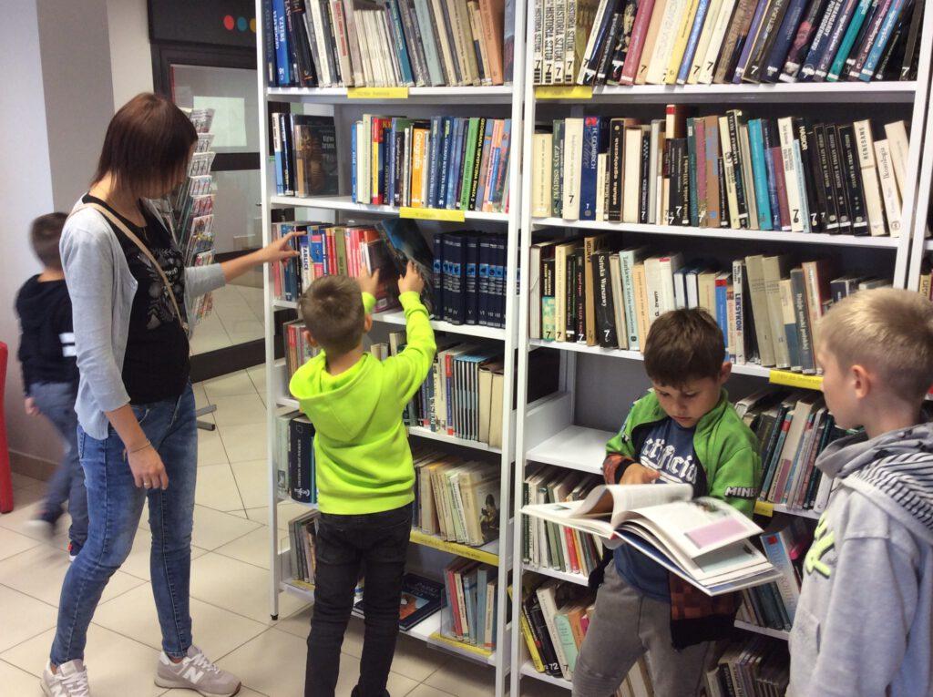 Może być zdjęciem przedstawiającym 1 osoba, dziecko, stoi, książka i w budynku.